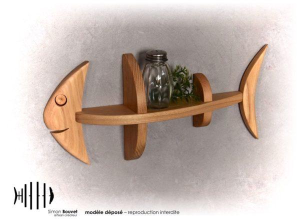 petite étagère murale en forme de poisson avec un flacon et une petite plante