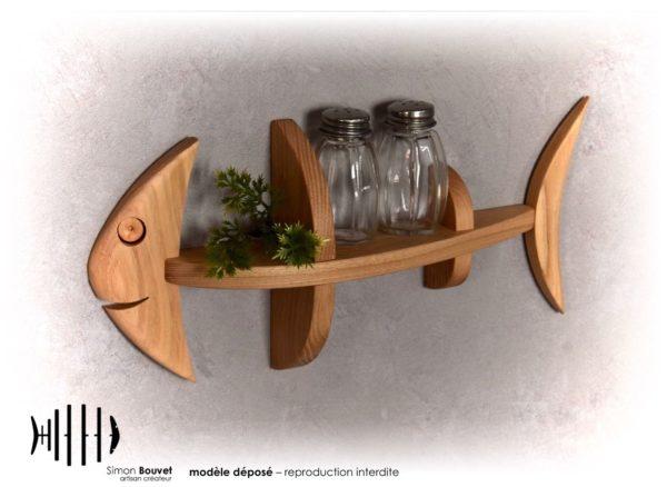 petite étagère murale en forme de poisson avec deux flacons et une petite plante