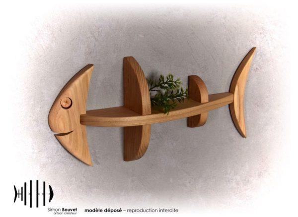 petite étagère murale en forme de poisson avec une petite plante